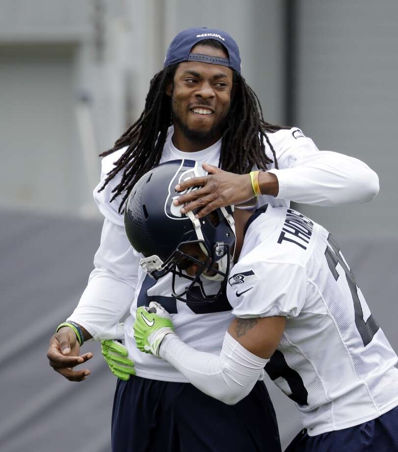 Richard Sherman, left, congratulates Earl Thomas on a defensive play at Seahawks OTAs on Thursday. Photo: Elaine Thompson, Associated Press
