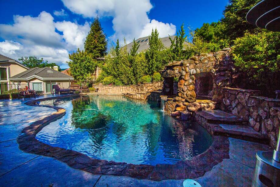 The backyard includes a pool and rock waterfall. Photo: Circlepix Photography