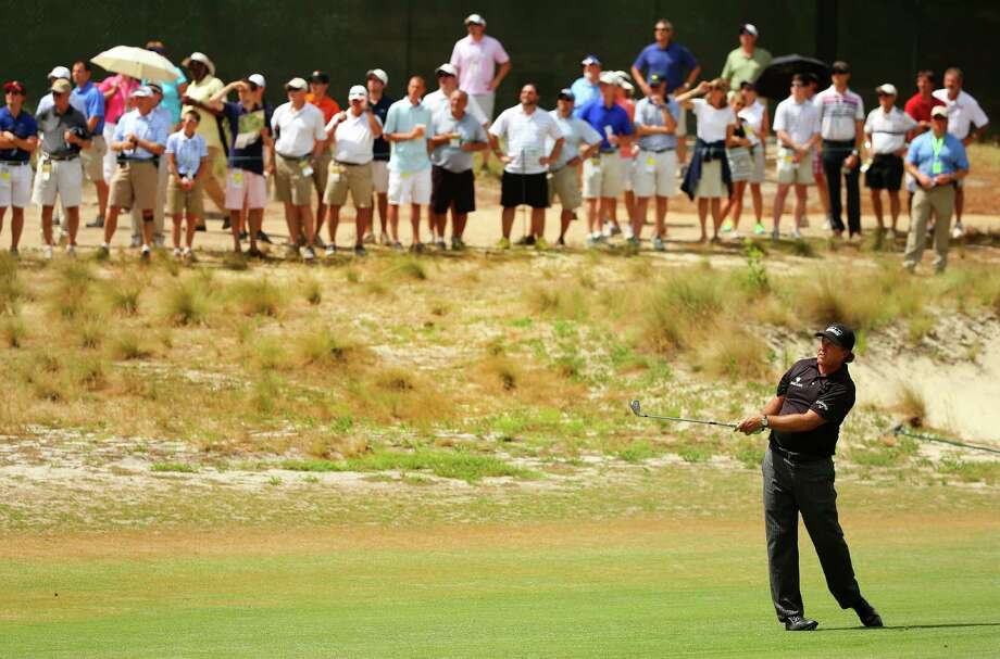 PINEHURST, NC - JUNE 12:  Phil Mickelson of the United States hits an approach shot on the fourth hole during the first round of the 114th U.S. Open at Pinehurst Resort & Country Club, Course No. 2 on June 12, 2014 in Pinehurst, North Carolina.  (Photo by Mike Ehrmann/Getty Images) ORG XMIT: 461911223 Photo: Mike Ehrmann / 2014 Getty Images