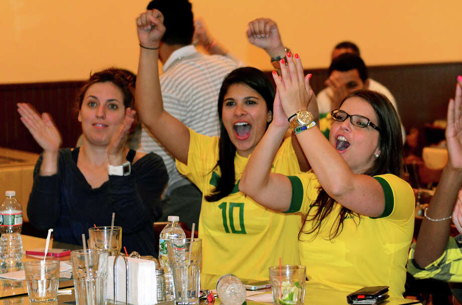 Kellen Nascimento, center, and her friend Taci D'Angelo, right, celebrate Brazil's win over Croatia, during a World Cup Soccer party held at Terra Brasilis Restaurant  in Bridgeport, Conn. on Thursday June 12, 2014. Photo: Christian Abraham / Connecticut Post