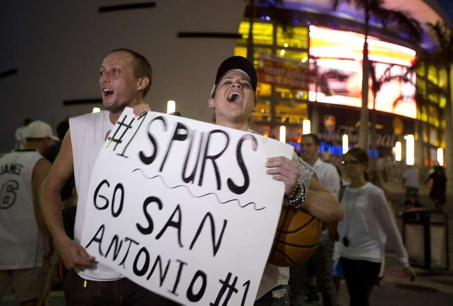 San Antonio tv reporter Fiona Gorostiza cheers for her team as she interviews Spurs fan Chaunce O'Connor outside the American Airlines Arena before Game 3 of the NBA basketball finals, Tuesday, June 10, 2014, in Miami.( AP Photo/J Pat Carter) Photo: J Pat Carter, Associated Press