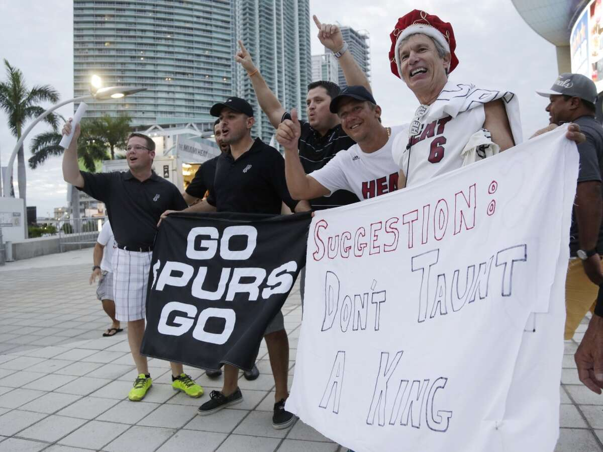 Miami Heat and San Antonio Spurs fans cheer outside the American Airlines Arena before during the start of Game 3 of the NBA basketball finals, Tuesday, June 10, 2014, in Miami. (AP Photo/Lynne Sladky)