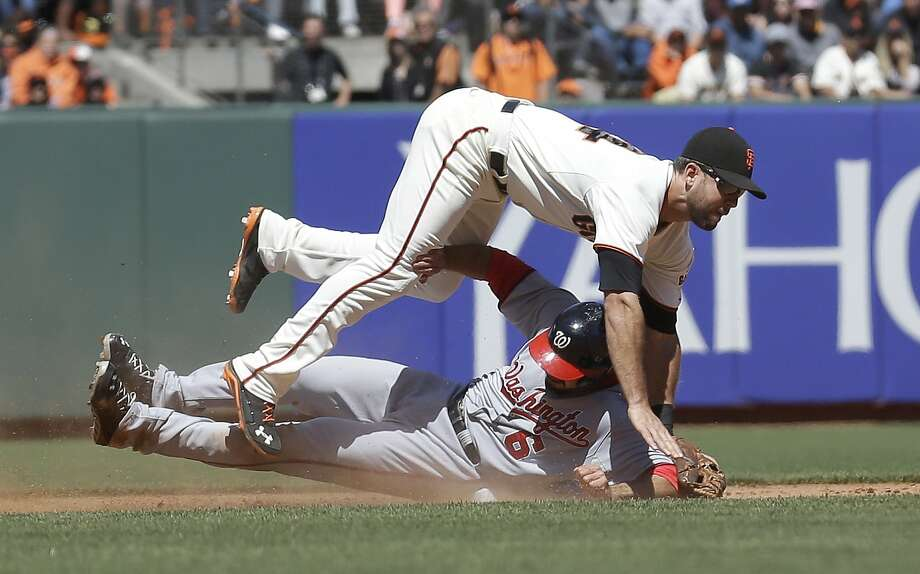Brandon Hicks tries to avoid landing on Anthony Rendon after throwing the relay to double up Jayson Werth at first base in the eighth inning. The Giants turned two double plays in the game. Photo: Jeff Chiu, Associated Press
