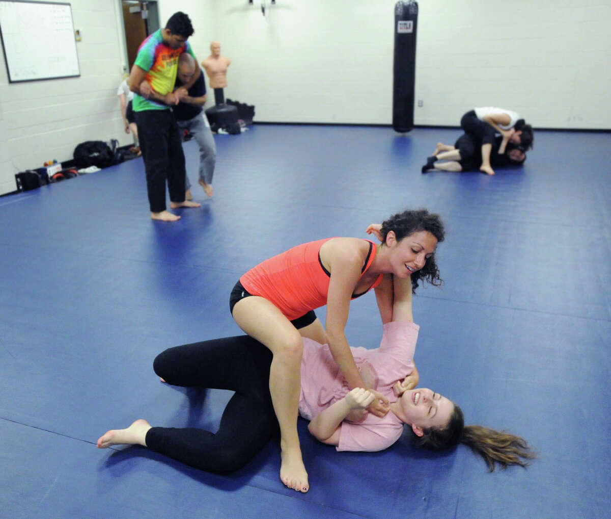 Greenwich Time reporter Brittany Lyte, at center on top, grapples with Rebecca Murray of Greenwich, during the Greenwich Police Department's Women's Self-Defense Class taught by Greenwich Police Officer Jeff Morris and Greenwich Police Detective Fred Quezada at Greenwich Police Headquarters, Thursday, June 12, 2014.