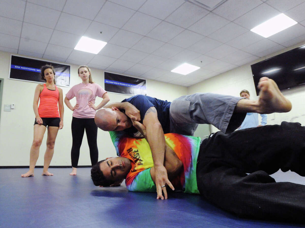 Greenwich Time reporter Brittany Lyte, left, and Rebecca Murray, center, of Greenwich, look on as Greenwich Police Officer, Jeff Morris, top right, and Greenwich Police Detective Fred Quezada, bottom, demonstrate a self-defense move during the self-defense class they were teaching at Greenwich Police Headquarters, Thursday, June 12, 2014.