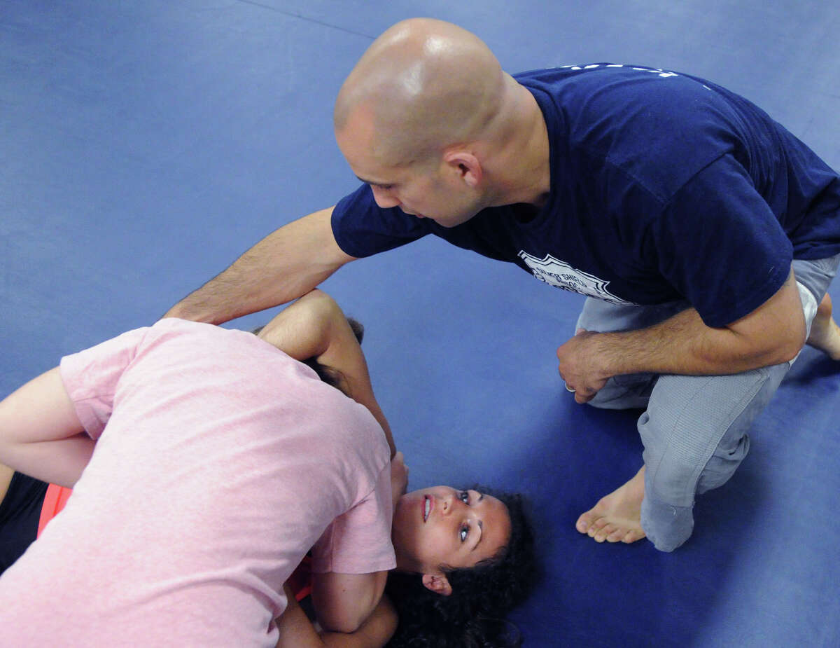 Greenwich Time reporter Brittany Lyte, center, puts Rebecca Murray, left, of Greenwich, in a headlock as Murray gets instruction about getting out of the headlock from Greenwich Police Officer, Jeff Morris, right, during the Greenwich Police Department's Women's Self-Defense Class taught by Morris and Greenwich Police Detective Fred Quezada at Greenwich Police Headquarters, Thursday, June 12, 2014.