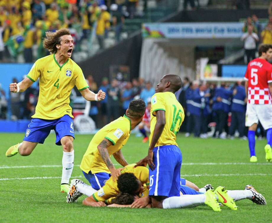 David Luiz (left) and his Brazilian teammates celebrate an injury time goal by Oscar (bottom of pile) as the World Cup's hosts got past Croatia 3-1 in the tournament opener. The Brazilians had to rally after conceding an own goal early in the first half. Photo: Adam Pretty / Getty Images / 2014 Getty Images