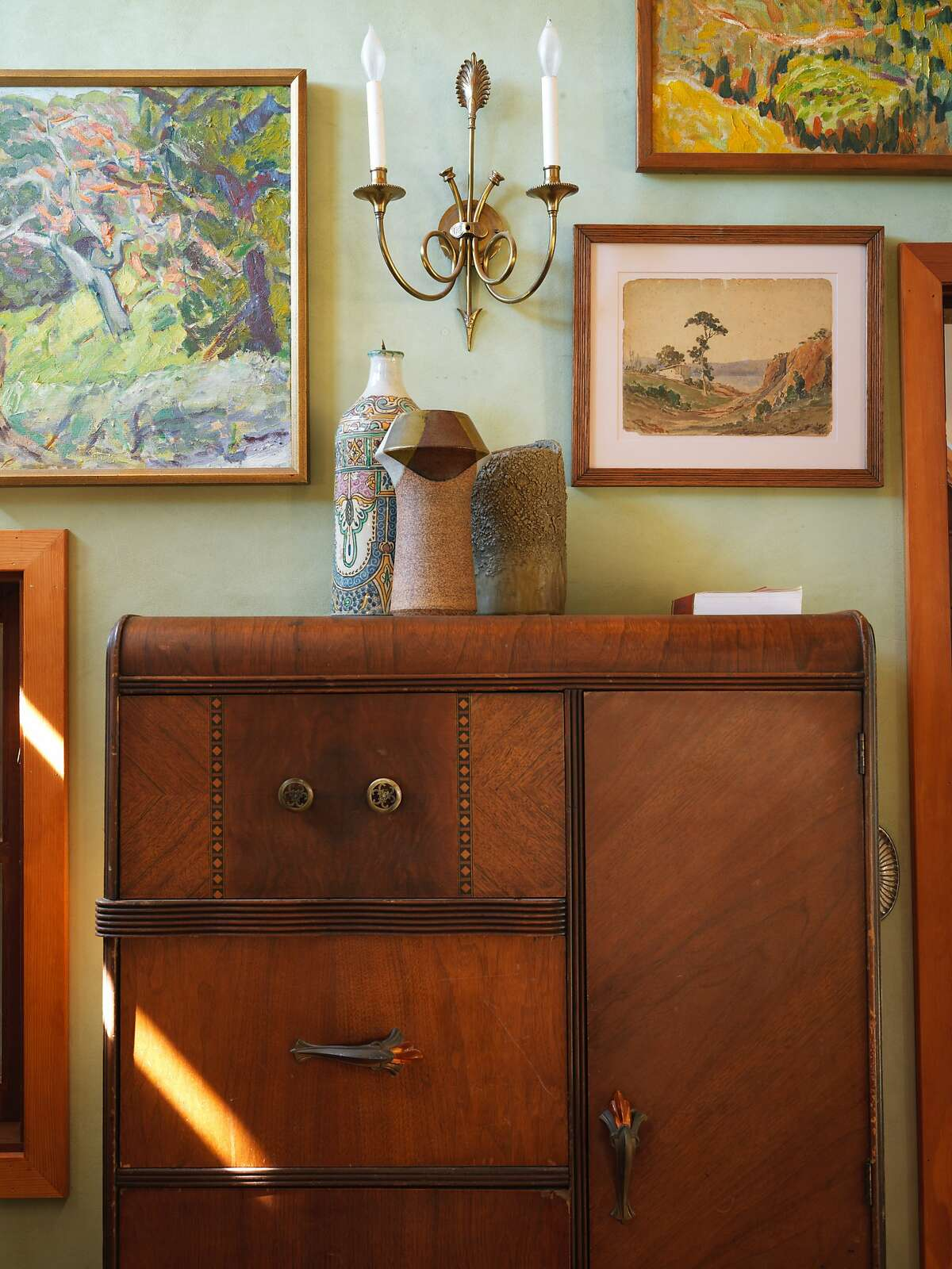 Like much of the other rooms in his house, the walls in Gaétan Caron's bedroom are covered in art hung salon-style. The art in this room share a landscape theme. Caron, co-owner of Lost Art Salon in San Francisco, lives off the grid in a custom house in the rolling hills west of Ukiah.