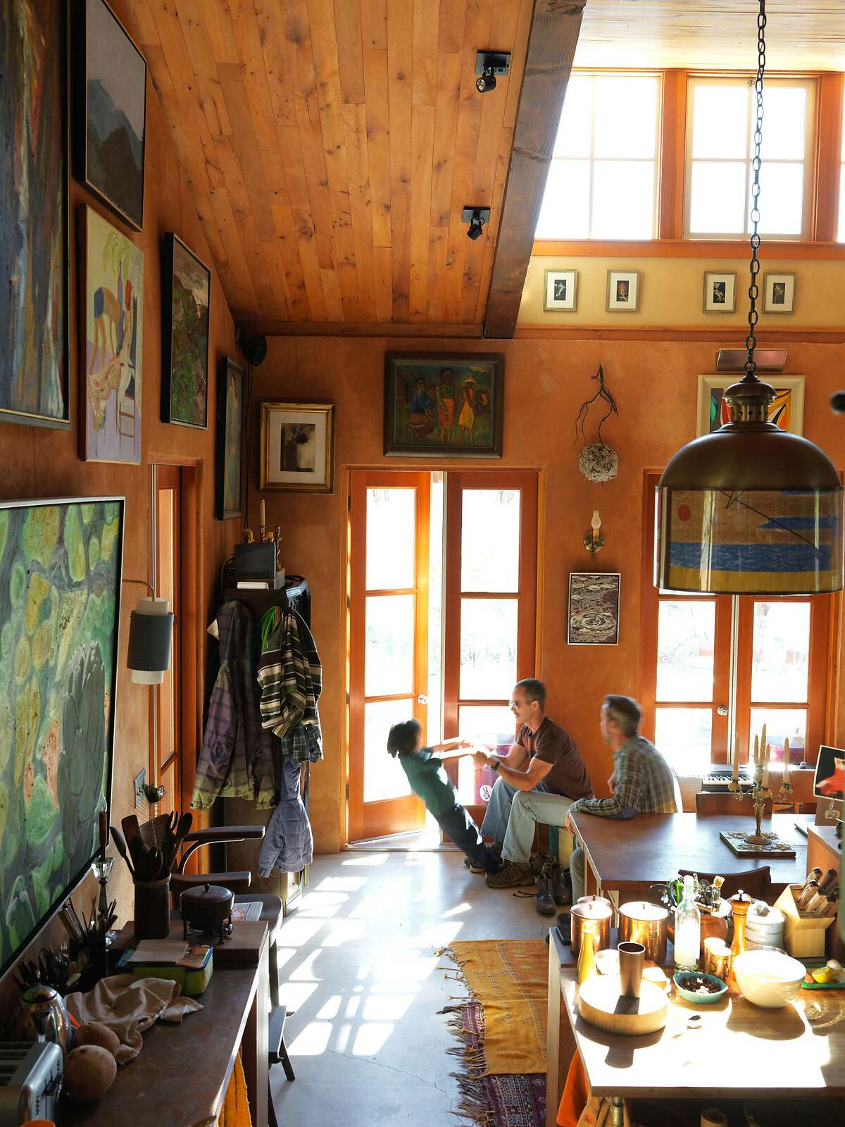 GaŽtan Caron, right, co-owner of Lost Art Salon, and his partner Mario platy with their 6-year-old son Jose Leo inside the great room of their home in the hills outside of Ukiah.