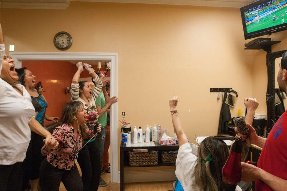 Employees and customers at Warren Joli Studio hair salon on Main Street in Danbury celebrate Brazil's second goal while watching the Brazil vs. Croatia World Cup opening match. Photo: Douglas Zimmerman, Courtesy