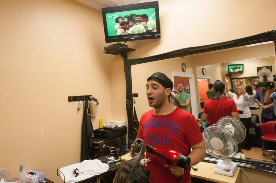 Employees and customers at Warren Joli Studio hair salon on Main Street in Danbury watch the Brazil vs. Croatia World Cup opening match. Photo: Douglas Zimmerman, Courtesy