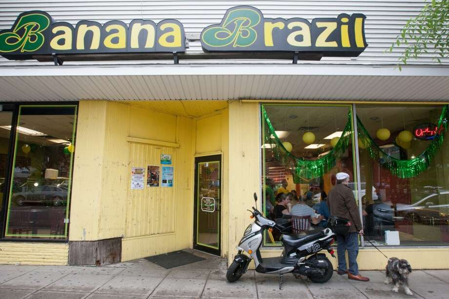 A pedestrian watches the Brazil vs. Croatia World Cup opening match from the window outside Banana Brazil restaurant on Main Street in Danbury, CT. Photo: Douglas Zimmerman, Courtesy
