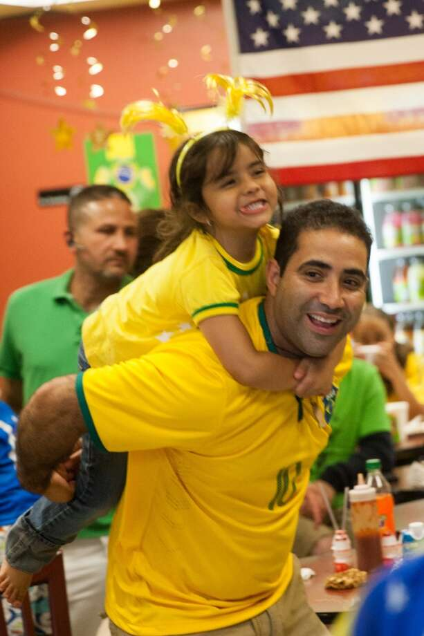 Banana Brazil owner Nilton Coelho gets a hug from his daughter Geovanna after watching the Brazil vs. Croatia World Cup opening match at his restaurant on Main Street in Danbury, CT. Photo: Douglas Zimmerman, Courtesy