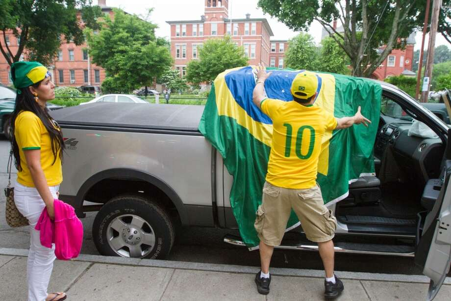 Brazilian Rubens DeSilva of Danbury drapes a large Brazil flag over his truck before he took part in a  impromptu parade down Main Street to celebrate Brazil's victory over  Croatia in their World Cup opening match. Photo: Douglas Zimmerman, Courtesy