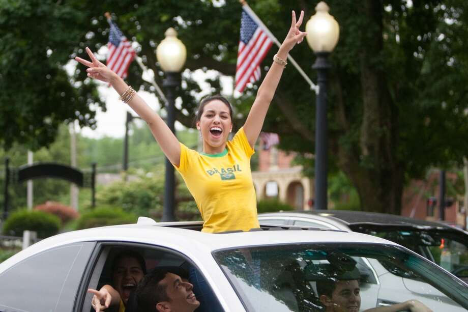 Brazil fan Viviane Gondinho of Danbury cheers while taking part in a impromptu parade down Main Street to celebrate Brazil's victory over Croatia in their World Cup opening match. Photo: Douglas Zimmerman, Courtesy