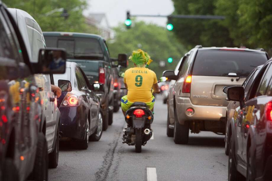 A Brazil fan drives and blows a whistle while taking part in a impromptu parade down Main Street to celebrate Brazil's victory over Croatia in their World Cup opening match. Photo: Douglas Zimmerman, Courtesy