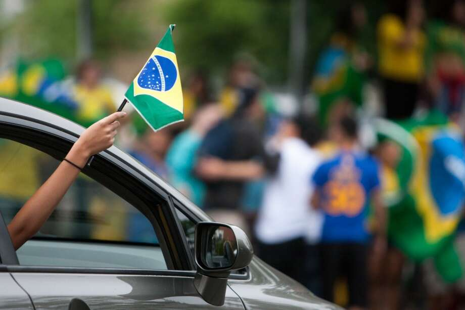 A Brazil fans holds a Brazil flag  while taking part in a impromptu parade down Main Street to celebrate Brazil's victory over Croatia in their World Cup opening match. Photo: Douglas Zimmerman, Courtesy