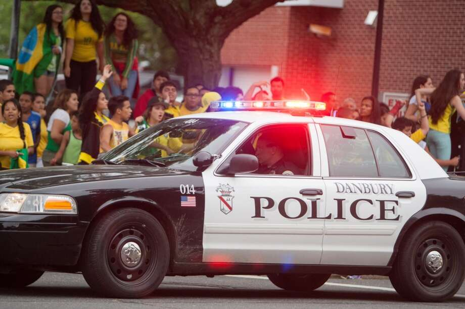 A Danbury police car patrols as Brazil fans cheer while taking part in a impromptu parade down Main Street to celebrate Brazil's victory over Croatia in their World Cup opening match. Photo: Douglas Zimmerman, Courtesy