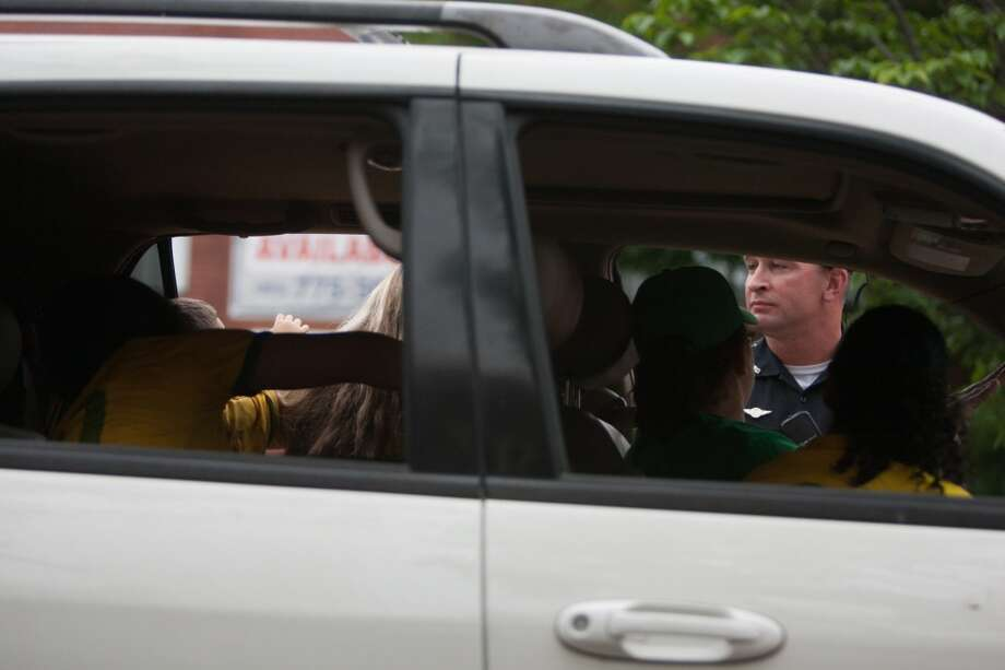 A Danbury police officer prepares to ticket a car full of Brazil fans that were taking part in a impromptu parade down Main Street to celebrate Brazil's victory over Croatia in their World Cup opening match.  The officer cited the car for having a passenger hang out the window. Photo: Douglas Zimmerman, Courtesy
