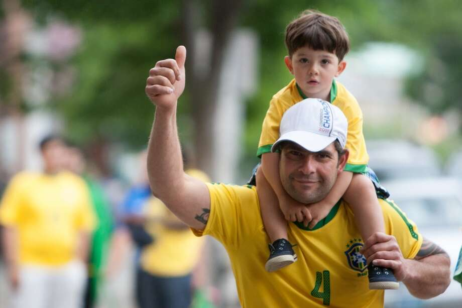 Brazil fan Walter deCastro of Bethel, CT and his son Igor give a thumbs up while taking part in a impromptu parade down Main Street to celebrate Brazil's victory over Croatia in their World Cup opening match. Photo: Douglas Zimmerman, Courtesy