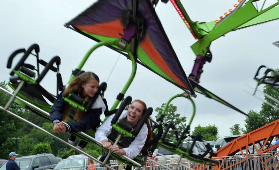 Fleur Byrne, 15, left, and Giselle Briand, 15, both of Westport, went for a spin on the Cliff Hanger as the Yankee Doodle Fair opened Thursday evening. Photo: Jarret Liotta / Westport News
