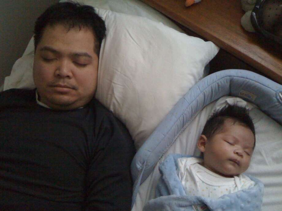 """We're both enjoying sleep but only when we actually sleep.  Baby fights off sleep but likes it when he gets it (even 2 years later).  Daddy likes it but doesn't get enough."" Photo: Submitted By Rafael Pacquing"
