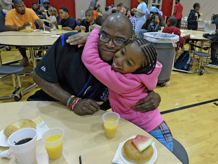 Tony Wilson gets a big hub from his daughter, Sequoia Hawkins, 8, while attending the Father's Day Breakfast program held Friday morning, June 13, 2014, at Pine Hills Elementary School in Albany, N.Y.   (Skip Dickstein/Times Union) Photo: SKIP DICKSTEIN / 00027353A