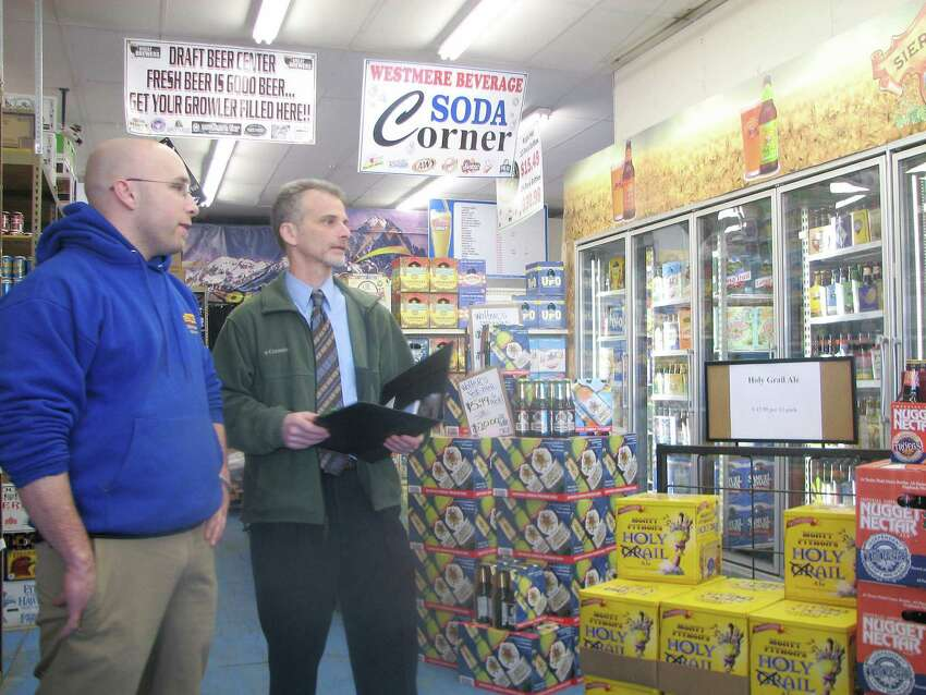 Jeremy Hosier, left, manager of Westmere Beverage in Guilderland shows the company's new energy-efficient cooler to Ben Greenberg of Rise Engineering. Rise installed new ceiling lighting in 2009 at the beer store that also cut its power (Larry Rulison / Times Union)