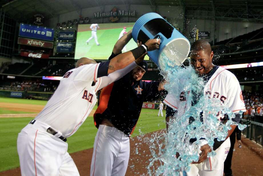 Houston Astros' Jon Singleton, left, and Jarred Cosart dump a water cooler on Chris Carter after Carter hit a walk off home run to defeat the Arizona Diamondbacks 5 - 4 during the 10th inning of a baseball game, Thursday, June 12, 2014, in Houston. (AP Photo/Patric Schneider) Photo: Patric Schneider, Associated Press / FR170473 AP