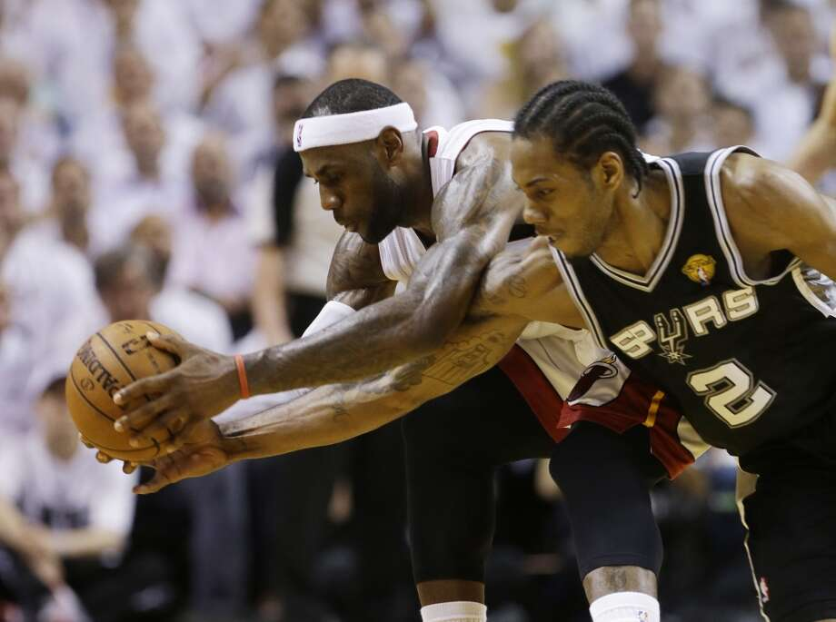 LeBron James, left, and Kawhi Leonard go after a loose ball during the first half in Game 4 of the NBA Finals. Photo: Lynne Sladky, Associated Press