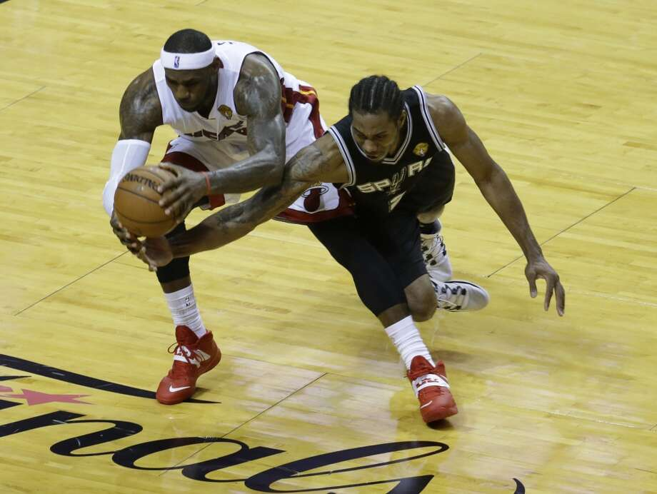 LeBron James, left, and Spurs forward Kawhi Leonard go after a loose ball during the first half in Game 4 of the NBA Finals. Photo: Wilfredo Lee, Associated Press