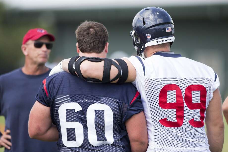 Defensive end J.J. Watt (99) puts his arm around guard Ben Jones (60) as they talk to defensive line coach Bill Kollar. Photo: Brett Coomer, Houston Chronicle