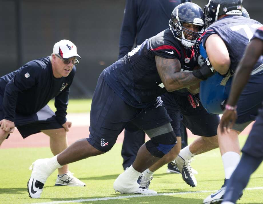 Duane Brown runs through a blocking drill as tight ends coach John Perry, left, looks on. Photo: Brett Coomer, Houston Chronicle