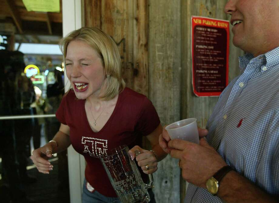 Amy  Barker, 22, is not enjoying the after tastes of the 32 ounce 'chugger' of beer  she drank where she dunked her graduation ring at the popular bor The Dixie Chicken in College Station as her dad Dan Barker observes.  Texas A&M University-College Station distributed approximately 3,500 graduation rings to students at the Clayton W. Williams, Jr. Alumni Center.  Photo by Mayra Beltran/ Houston Chronicle Photo: Mayra Beltran, HOUSTON CHRONICLE / HOUSTON CHRONICLE