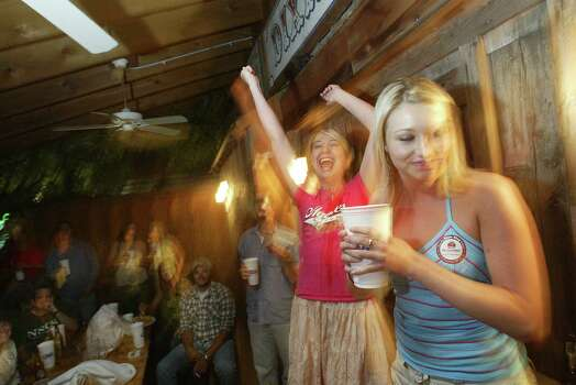 (LEFT TO RIGHT) Lemoine Knox, 20, encourages her hometown friend Tina Hall, 22, of Coleman Texas, to finish drinking her 'chugger' where Tina dunked her graduation ring at the popular Dixie Chicken in College Station.  Texas A&M University-College Station distributed approximately 3,500 graduation rings to students at the Clayton W. Williams, Jr. Alumni Center.  Photo by Mayra Beltran/ Houston Chronicle Photo: Mayra Beltran, HOUSTON CHRONICLE / HOUSTON CHRONICLE