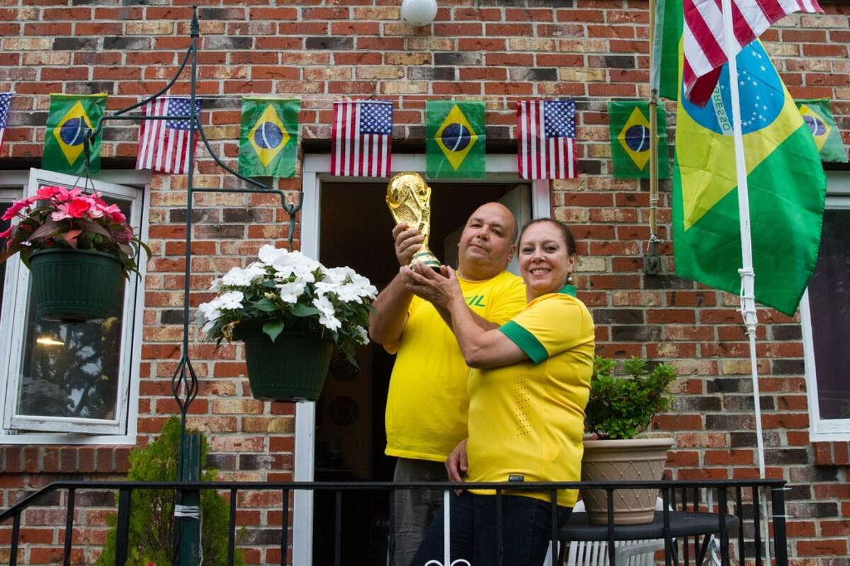 Brazillian Joao Oliveria and his wife Elaine hold a replica of the World Cup trophy at their home in Danbury, CT during halftime of the Brazil vs. Croatia World Cup opening match.