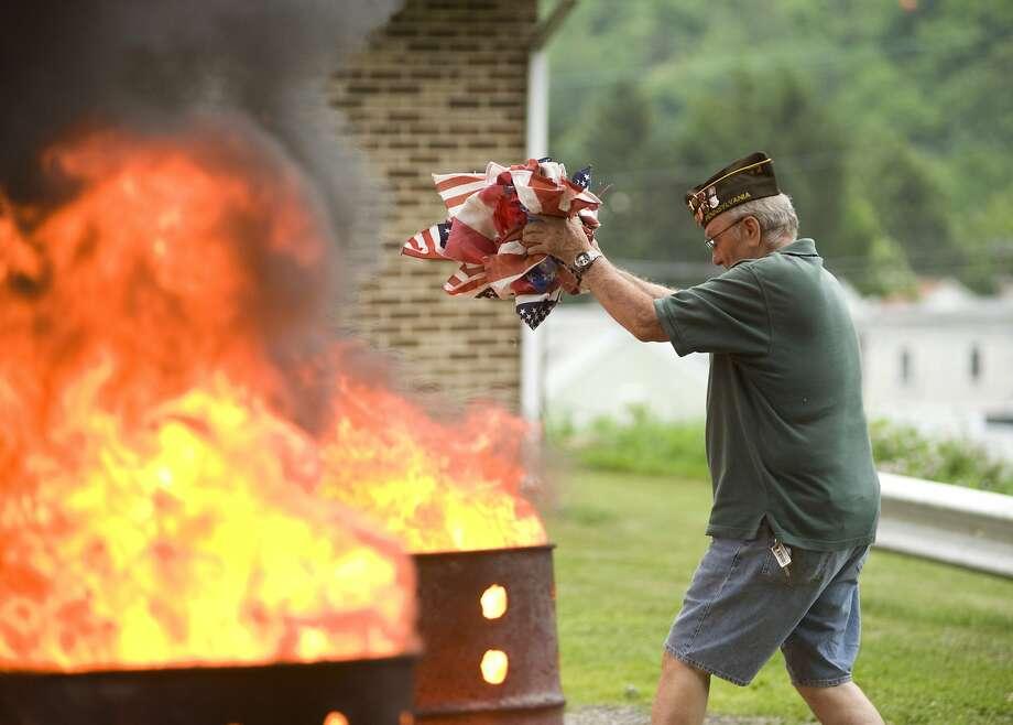 "Out in a blaze of Old Glory:Ralph Schenewerk of VFW Post 317 ""retires"" a flag at the Coal Township   municipal building near Shamokin, Pa. Photo: Larry Deklinski, Associated Press"
