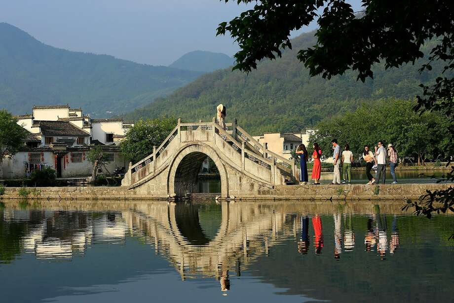 Tourists cross a bridge at Hongcun Village, China, an ancient village with a 900-year 