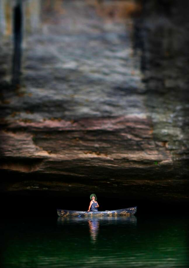 Tranquil paddle: Debbie Doss glides into a shallow cave under the stone cliffs of Arkansas' Buffalo River near Mount Judea. Photo: Jim Weber, Associated Press