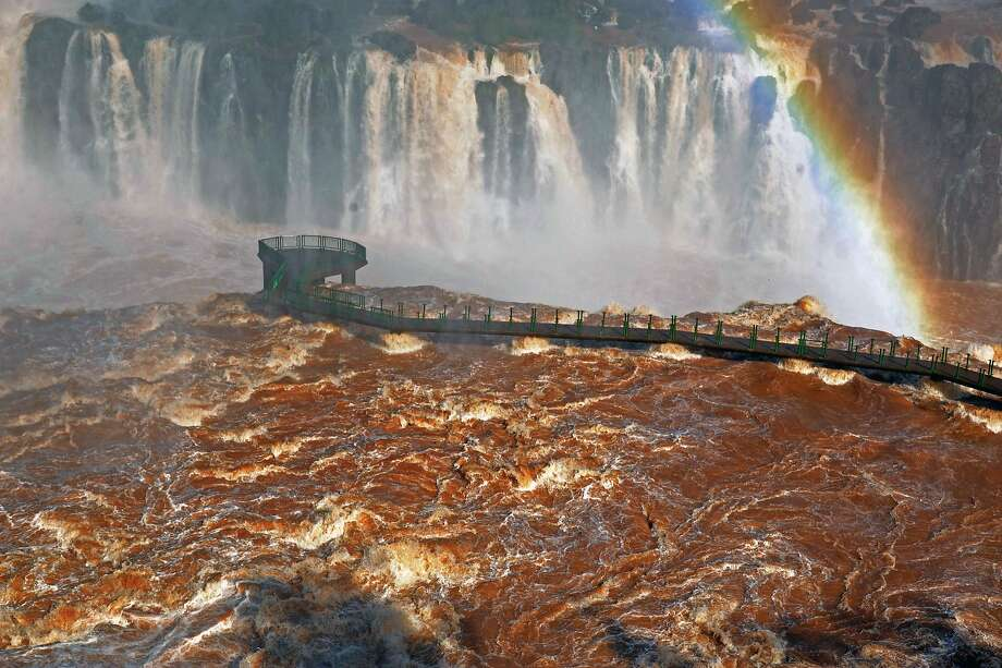 Roiling watersbatter an observation bridge at the famous Iguazu Falls in Foz do Iguazu, Brazil, as 