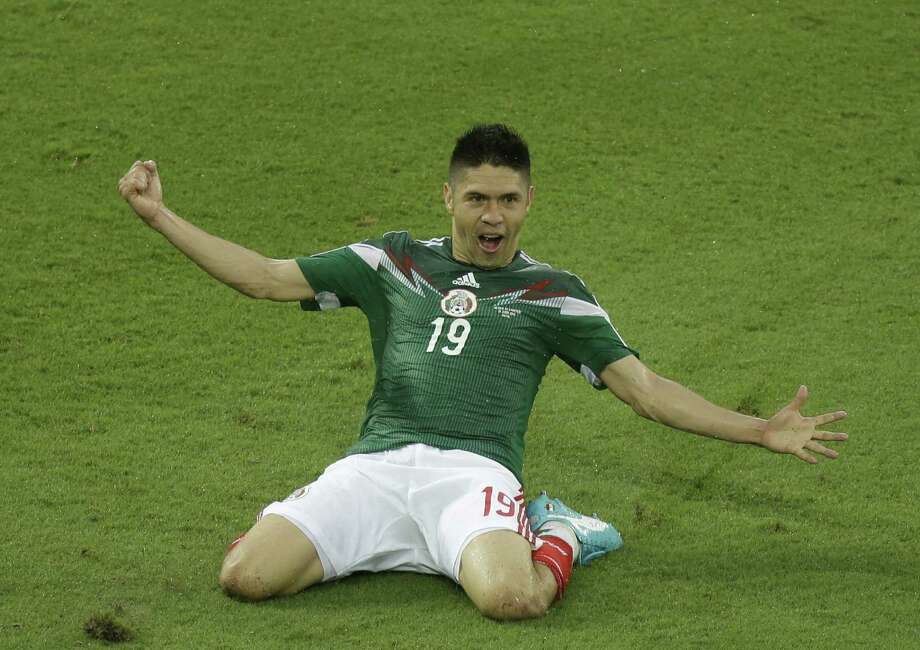 Mexico's Oribe Peralta celebrates after scoring during the group A World Cup soccer match between Mexico and Cameroon in the Arena das Dunas in Natal, Brazil, Friday, June 13, 2014.  (AP Photo/Hassan Ammar) Photo: Hassan Ammar, Associated Press / AP