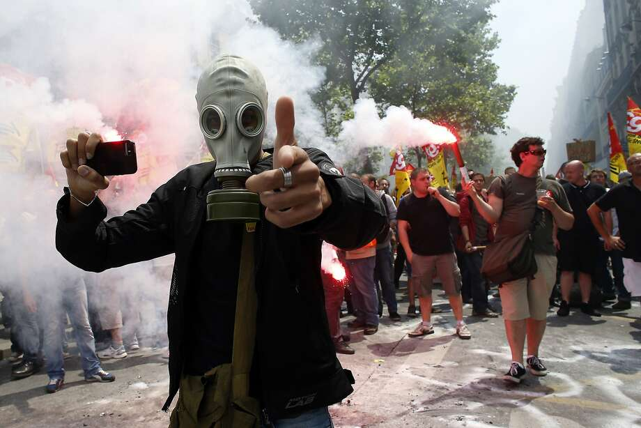 Prepared for the worst:A protester expecting a tear-gas attack takes cell phone photos of a rally by striking employees of the French state rail company SNCF near the Transport Ministry in Paris. French rail workers are opposing government proposals to reduce the transportation sector's soaring debt. Photo: Thomas Samson, AFP/Getty Images