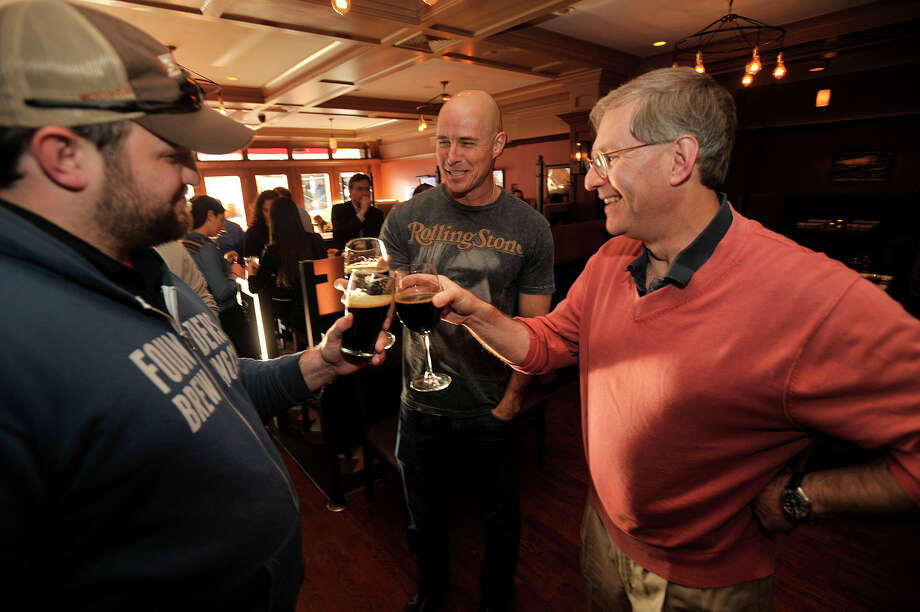 John Abercrombie, left, clinks glasses with Bob Surgent, center, and Brett Steenbarger at Cask Republic in Stamford, Conn., on Wednesday, April 23, 2014. Cask Republic is among the local restaurants where reservations can be made through OpenTable, the booking site that has just been bought by Norwalk's Priceline Group. Photo: Jason Rearick / Stamford Advocate