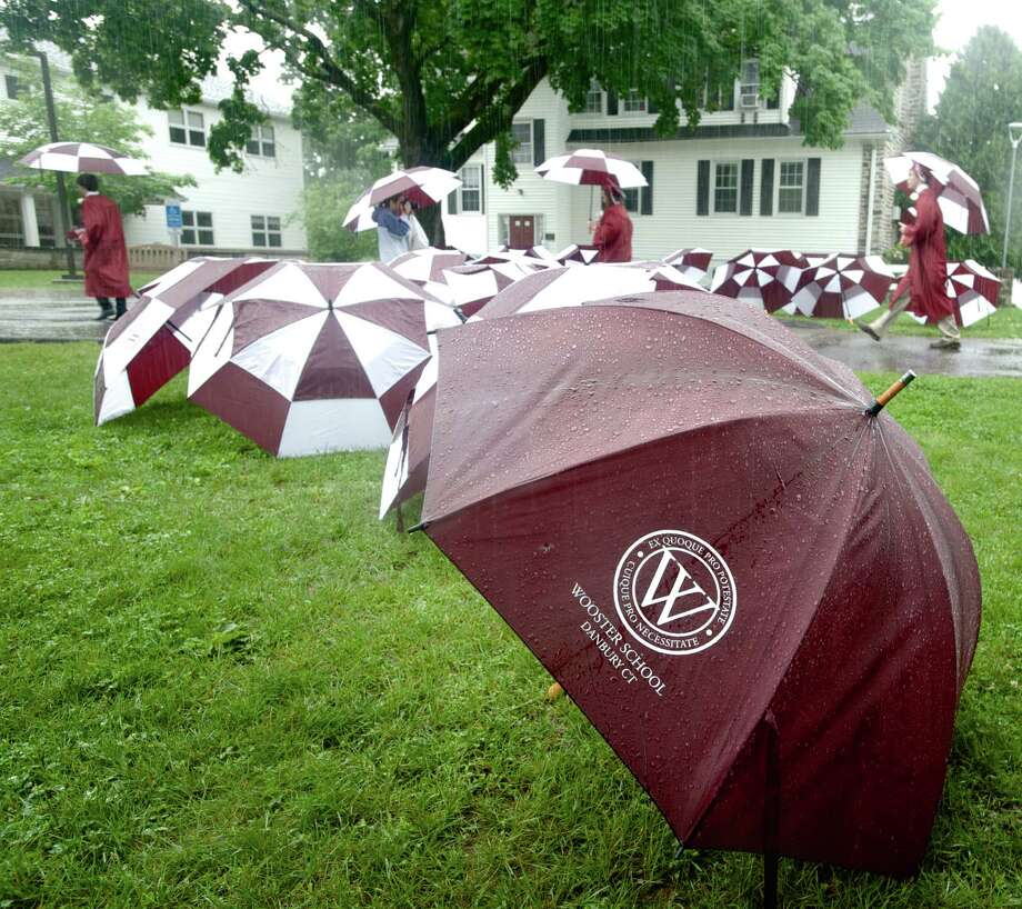 Graduates pick up their umbrellas as they leave the 2014 Graduation Ceremony for Wooster School, in Danbury, Conn, on Friday morning, June 13, 2014. Photo: H John Voorhees III / The News-Times Freelance