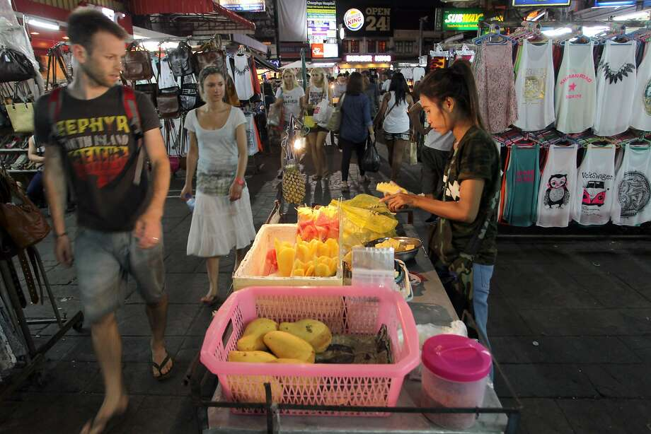Tourists walk past a Thai fruit vendor after the curfew was lifted in Bangkok, Thailand Friday, June 13, 2014. Thailand's military government has fully lifted a curfew it imposed nationwide after seizing power last month, saying there is no threat of violence. (AP Photo/Apichart Weerawong) Photo: Apichart Weerawong, Associated Press