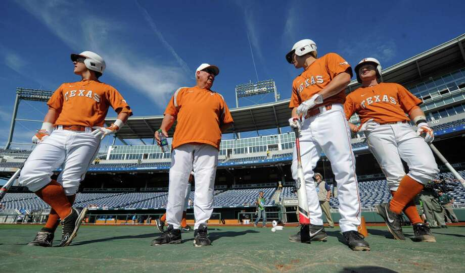 Texas infielder Brooks Marlow, left, coach Augie Garrido, infielder Madison Carter, second right, and Zane Gurwitz, right, are seen during team practice, Friday, June 13, 2014, ahead of the NCAA baseball College World Series tournament at TD Ameritrade Park in Omaha, Neb.. Texas plays UC Irvine on Saturday. (AP Photo/Dave Weaver) Photo: Dave Weaver, Associated Press / FR67562 AP