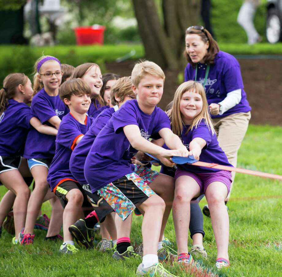 On Field Day at Pear Tree Point School Lanie Durkin, Holly Silva, Dagny Streit, Baker Beck, Gracie Barker and Sam Eglin, from left to right, put forth great effort to dislodge the red team in the final tug-o-war event as they are cheered on by third-grade teacher Maria Ferretti. Photo: Contributed Photo, Contributed / Darien News
