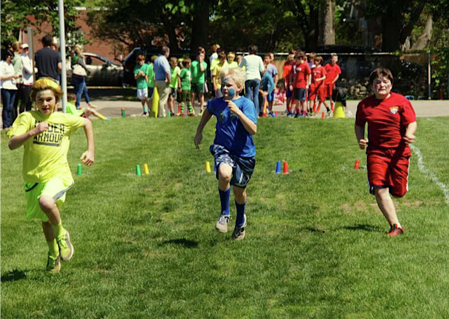 Hindley School students Reed Tarleton, Owen O'Brien and Ryan Plank, from left to right, race each other in the 50-yard dash during the annual Field Day. Photo: Contributed Photo, Contributed / Darien News