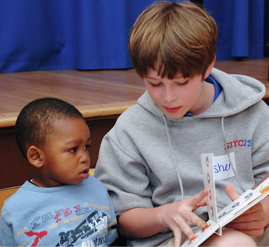 Fifth-grader Asher Silverman reads to a preschooler during Pear Tree Point School's community service literacy project with Family and Children's Agency. Photo: Contributed Photo, Contributed / Darien News