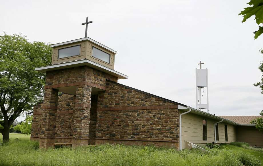 A cell tower rises behind the Resurrection Lutheran Church in Ankeny, Iowa. Photo: Charlie Neibergall, Associated Press